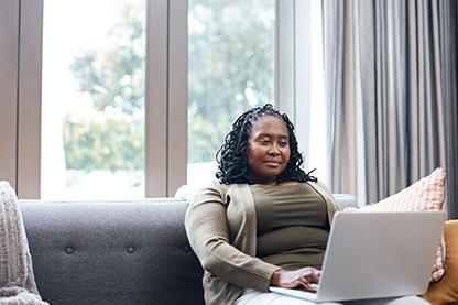 Image: Woman on couch with laptop